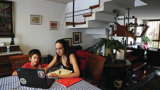 In this Monday photo, Nadia Muñoz helps her son Luka with his online lessons from a private Catholic school, at their home in an upper-middle-class neighborhood of Lima, Peru. For the makeup artist and her family, Lima's near-total 15-day quarantine hasn't been too disruptive.
