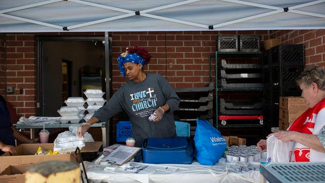 Katica Frierson, a food associate at Randolph Howell Elementary School, prepares boxed lunches for distribution on on Friday, March 27, 2020.