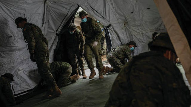 Spanish Army soldiers mount a tent to be used by hospital patients during the coronavirus outbreak in Madrid, Spain, Monday. Bells tolled in Madrid's deserted central square and flags were lowered in a day of mourning Monday as Spain raced to build field hospitals to treat an onslaught of coronavirus patients. The new coronavirus causes mild or moderate symptoms for most people, but for some, especially older adults and people with existing health problems, it can cause more severe illness or death.