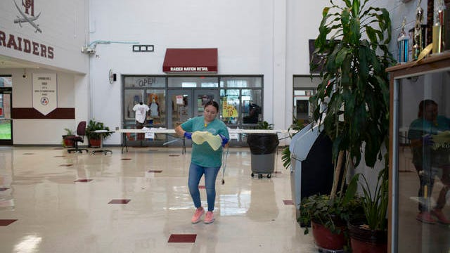 Yesenia Reyes cleans the entrance to Spring Hill High School on Wednesday, March 18, 2020.