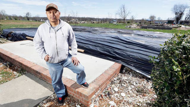 In this March 26 photo, Jose Cojom stands on the front step of what remains of his home after it was destroyed by a tornado in Cookeville, Tenn. Like thousands of other Middle Tennesseans, Cojom's life has been upended by back-to-back disasters. Residents still reeling from the deadly twisters of March 3 now have to confront life in the age of coronavirus.