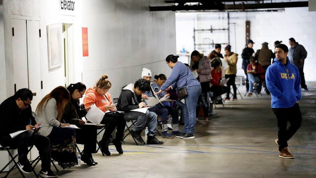 In this March 13, 2020 file photo, unionized hospitality workers wait in line in a basement garage to apply for unemployment benefits at the Hospitality Training Academy in Los Angeles. More than 6.6 million Americans applied for unemployment benefits last week, far exceeding a record high set just last week, a sign that layoffs are accelerating in the midst of the coronavirus.