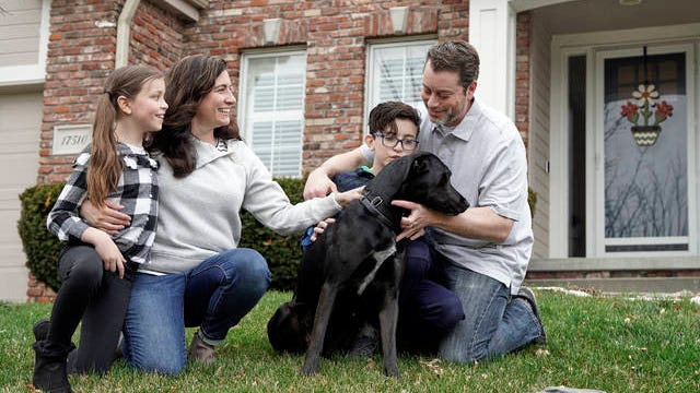 Kim Simeon; her husband, Adam; and children, Annabel, 9, and Brennan, 11, pose for a photo with Nala, a dog they are fostering, in Omaha, Neb., on March 27. The Simeon family was headed home to Omaha from a much-needed Smoky Mountains vacation when Kim Simeon spotted a social media post from the Nebraska Humane Society, pleading with people to consider fostering a pet.