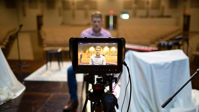Maury Hills Church Lead Pastor Russ Adcox sits behind a camera on the stage of the church worship hall in Columbia on Sunday.