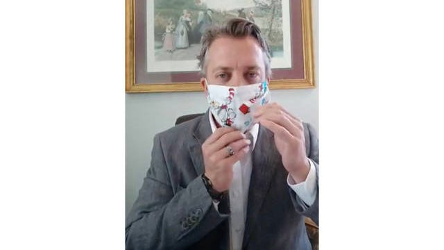 Maury County Mayor Andy Ogles demonstrates the use of a face mask during a live community update on Monday.