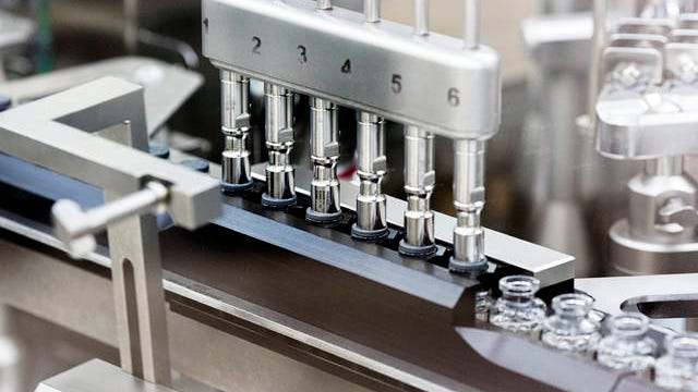 In this March 2020 photo provided by Gilead Sciences, rubber stoppers are placed onto filled vials of the investigational drug remdesivir at a Gilead manufacturing site in the United States. Given through an IV, the medication is designed to interfere with an enzyme that reproduces viral genetic material.