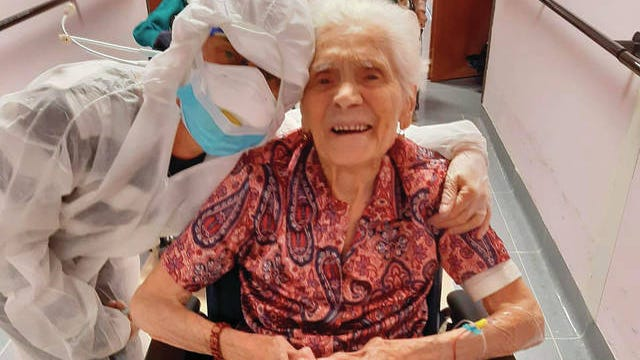 """In this photo taken on April 1, 103-year-old Ada Zanusso, poses with a nurse at the old people's home """"Maria Grazia"""" in Lessona, northern Italy, after recovering from Covid-19 infection."""