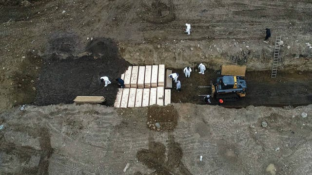 Workers wearing personal protective equipment bury bodies in a trench on Hart Island, Thursday, in the Bronx borough of New York. On Thursday, New York City's medical examiner confirmed that the city has shortened the amount of time it will hold on to remains to 14 days from 30 days before they will be transferred for temporary internment at a City Cemetery. Earlier in the week, Mayor Bill DeBlasio said that officials have explored the possibility of temporary burials on Hart Island, a strip of land in Long Island Sound that has long served as the city's potter's field.