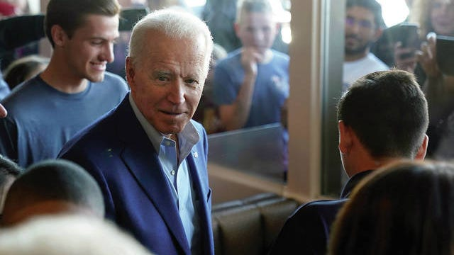Democratic presidential candidate former Vice President Joe Biden talks with customers as people watch through the windows at the Buttercup Diner during a campaign stop in Oakland, Calif., Tuesday, March 3, 2020.