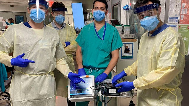 In this March 30 photo provided by Mount Sinai, from left, Drew Copeland, RPSGT; Dr. Thomas Tolbert, Dr. Brian Mayrsohn, and Dr. Hooman Poor, stand with a ventilator prototype they developed from a sleep apnea machine at Mount Sinai hospital in New York.