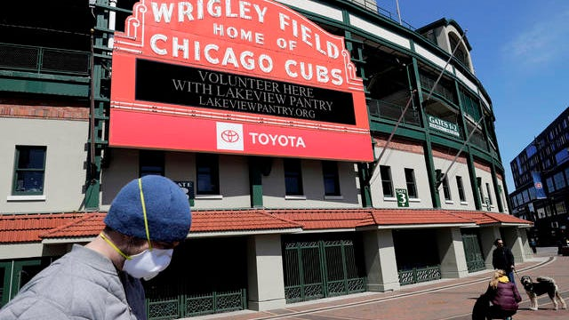 In this April 16 file photo, Wrigley Field's marquee displays Lakeview Pantry volunteer information in Chicago. With no games being played, recent sports headlines have centered around hopes and dreams -- namely, the uncharted path leagues and teams must navigate to return to competition in the wake of the pandemic.
