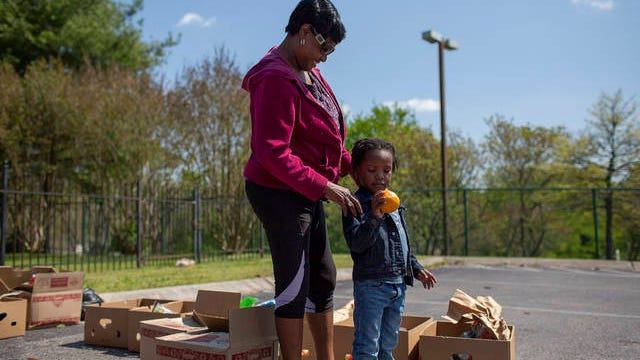 Chetika Dunlap and Kayson Thomas look through donations of produce at the Family Center in Columbia on Monday, April 20, 2020.