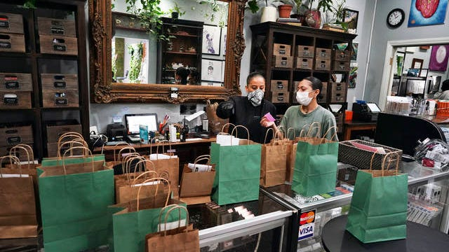 In this April 16 photo, wearing a protective mask and gloves, budtenders prepare orders for customers to pick-up at The Higher Path cannabis dispensary in the Sherman Oaks section of Los Angeles.