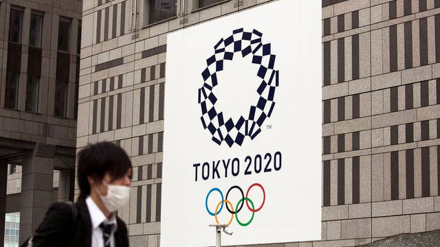 A man walks past a large banner promoting the Tokyo 2020 Olympics in Tokyo, Monday, March 23, 2020.