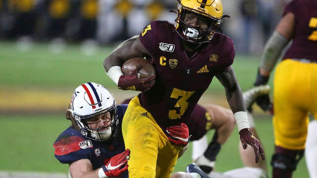 In this Nov. 30, 2019, file photo, Arizona State's Eno Benjamin (3) slips the tackle of Arizona's Colin Schooler (7) during the second half of an NCAA college football game in Tempe, Ariz. Five NFL prospects, including Benjamin, are being featured in a Panini docu-series that chronicles their paths to the NFL. With the coronavirus outbreak, teams were not allowed to visit with prospects. These five players get to tell their stories, giving them an advantage over the rest of the field.