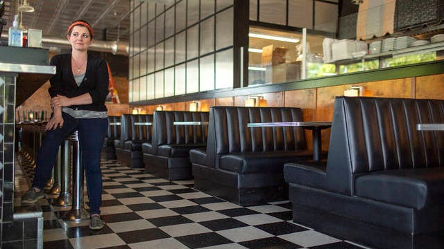 Manager Clair Randolph sits at the bar of the Mt. Pleasant Grille in Mt. Pleasant on Friday. The restaurant continues to offer take-out options during the shutdown to prevent the spread of the coronavirus.
