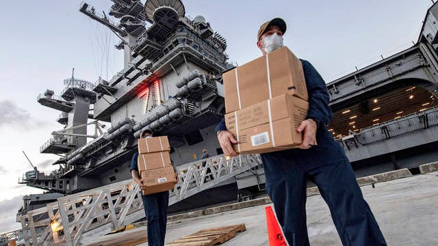 In this April 7 photo released by the U.S. Navy, sailors assigned to the aircraft carrier USS Theodore Roosevelt move ready to eat meals for sailors who have tested negative for COVID-19 and are being taken to local hotels in an effort to implement social distancing at Naval Base Guam. People in Guam are used to a constant U.S. military presence on the strategic Pacific island, but some are nervous as hundreds of sailors from the coronavirus-stricken Navy aircraft carrier flood into hotels for quarantine. Officials insist they have enforced strict safety measures.