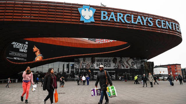 In this March 12,, file photo, pedestrians walk past the Barclays Center, which is home to the Brooklyn Nets, in the Brooklyn borough of New York.
