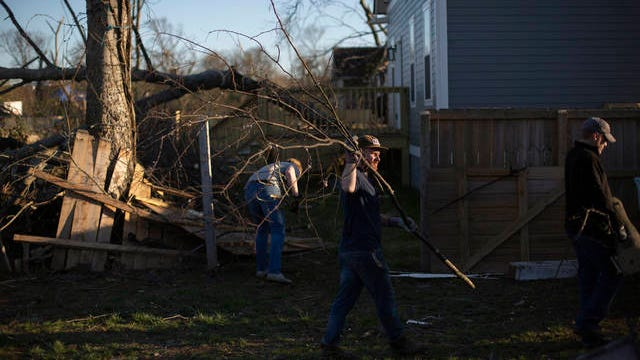Asher Weinstein, center, carries a piece of a downed tree from the backyard of a home in the Ossage/North Fisk neighborhood of Nashville during a tornado cleanup effort on Thursday, March 5, 2020.