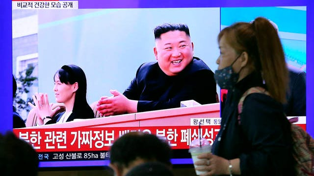 A woman passes by a TV screen showing an image of North Korean leader Kim Jong Un and his sister Kim Yo Jong during a news program at the Seoul Railway Station in Seoul, South Korea, Saturday. Kim made his first public appearance in 20 days as he celebrated the completion of a fertilizer factory near Pyongyang, state media said Saturday, ending an absence that had triggered global rumors that he was seriously ill.