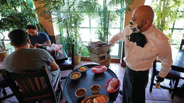 Waiter Marcos Huerta, right, serves a grill of fajitas at El Tiempo Cantina on Friday in Houston. The restaurant reopened their dining room for table service, with limited capacity, Friday. Texas' stay-at-home orders due to the COVID-19 pandemic have expired and Texas Gov. Greg Abbott has eased restrictions on many businesses that have now opened.