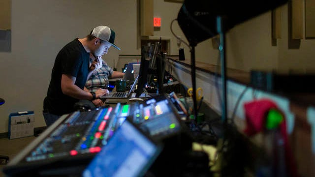 Maury Hills Church Worship Leader Scott Utter monitors a Palm Sunday service as it is being broadcast on YouTube and Facebook from a control center inside the Columbia worship hall on Sunday, April 5, 2020.