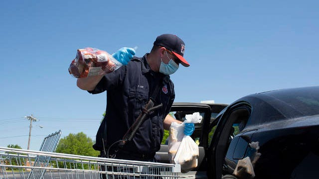 Columbia Firefighter Riley Luke loads food into a car during a food drive hosted by One Generation Away at Columbia State Community College on Saturday May 2, 2020.