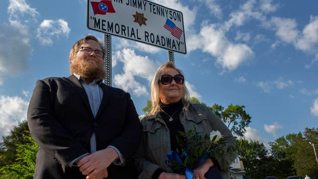 Evan Bearden, the son of the late Maury County Sheriff's Department Captain Jimmy Tennyson, and Dee Tennessean, his widow, stand in front of a sign commemorating Iron Bridge Road east of Columbia in honor of Tennyson during a memorial ceremony on Wednesday, May 6, 2020.