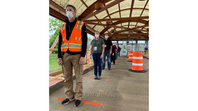 Todd Haylett, facilities manager, and Amber Hopper, business manager wait in a socially-distanced queue to enter the General Motors assembly plant in Spring Hill on Monday. The day marked the return of the first group of team members to the plant following a shutdown to prevent the spread of the coronavirus.