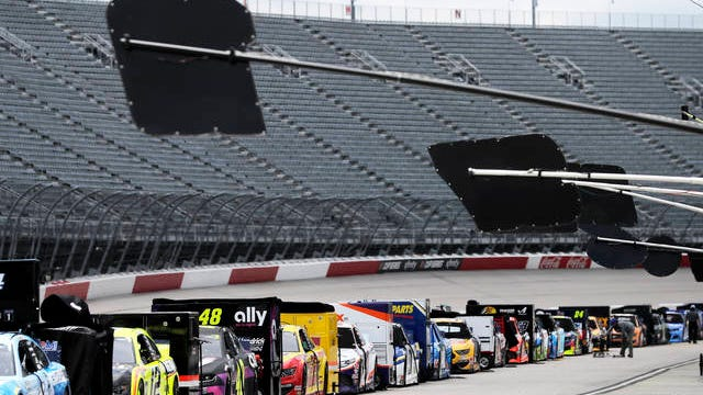 Cars are lined up with empty grandstands behind them before the NASCAR Cup Series auto race on Sunday in Darlington, S.C.