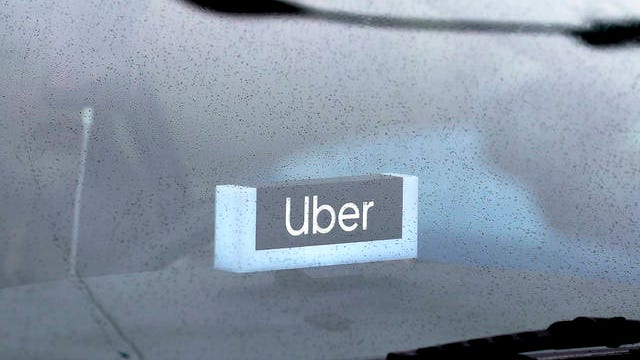 An Uber sign is displayed inside a car in Chicago on May 15. Beginning Monday, both riders and drivers have to wear masks or face coverings for the duration of Uber trips.