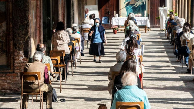 Faithful attend a Mass in the courtyard of La Fontana church, in Milan, Italy on Monday. On Monday, Italians enjoyed a first day of regained freedoms, including being able to sit down at a cafe or restaurant, shop in all retail stores or attend church services such as Mass.