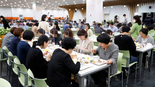 People eat lunch at tables equipped with plastic barriers to prevent any possible spread of the new coronavirus at the cafeteria of Seoul City Hall in Seoul, South Korea on Wednesday.