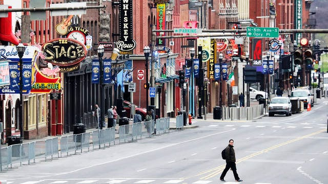A man walks across Broadway, where the streets are usually filled and the sidewalks are usually crowded on March 23 in Nashville. More cities and counties in Tennessee have issued strict orders for nonessential businesses to shut down temporarily and people to stay at home as much as possible to curb the spread of the coronavirus.