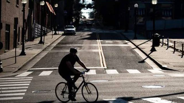 A bicyclist passes Church St. on First Ave. in downtown Nashville on March 25.
