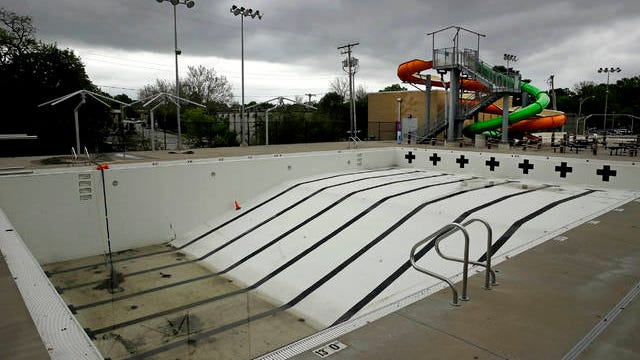 In this photo taken May 15, the public pool in Mission, Kan. is lifeless as plans remain in place to keep the pool closed for the summer to help prevent the spread of COVID-19. As warm weather approaches and many public pools remain closed there has been a surge of people using backyard pools as well at taking to water activities on lakes and rivers to get out and cool off.