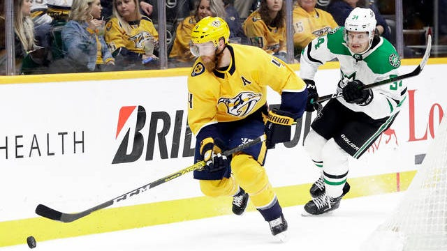 Nashville Predators defenseman Ryan Ellis (4) moves the puck ahead of Dallas Stars right wing Denis Gurianov (34), of Russia, in the third period of an NHL hockey game on March 5, 2020 in Nashville. The Predators won 2-0.