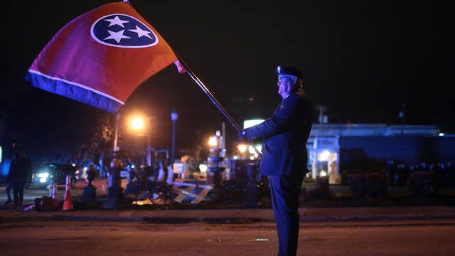 Local Knights of Columbus member Larry Watts stands waiting to march holding the Tennessee flag before the start of the the Columbia Main Street Christmas Parade on Monday, Dec. 2, 2019.