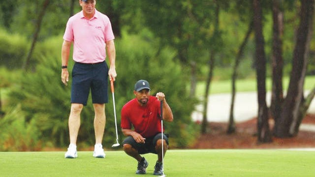 Tiger Woods lines up a putt with an assist from former University of Tennessee and Super Bowl champion quarterback Peyton Manning.