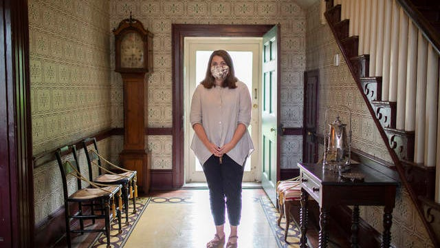 Curator Candice Roland Candeto stands inside the foyer of the James K. Polk Home and Museum in Columbia, Tenn., on the museum's first day of welcoming visitors following an extended closure to prevent the spread of the coronavirus on Tuesday, May 26, 2020.