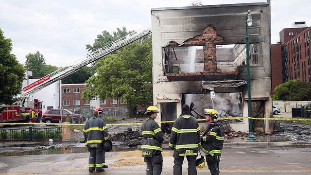Firefighters stand as an aerial hose sends water on hot spots of a building destroyed near the Minneapolis Police Third Precinct Thursday in Minneapolis, after a night of rioting and looting as protests continue over the death of George Floyd, who was seen on video gasping for breath during an arrest in which an officer kneeled on his neck.