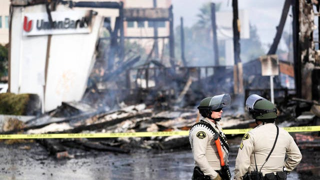 San Diego County sheriff officers stand guard in front of a burning bank building after a protest over the death of George Floyd on Sunday in La Mesa, Calif. Protests were held in U.S. cities over the death of Floyd, a black man who died after being restrained by Minneapolis police officers on May 25.