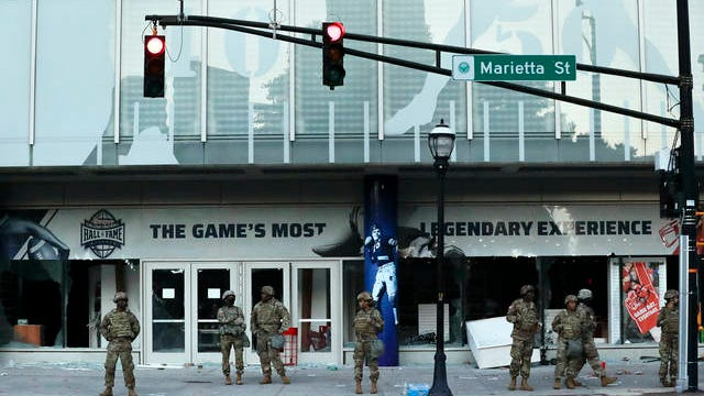 The Georgia National Guard lines up in front of the of the College Football Hall of Fame in the aftermath of a demonstration against police violence on Saturday in Atlanta.