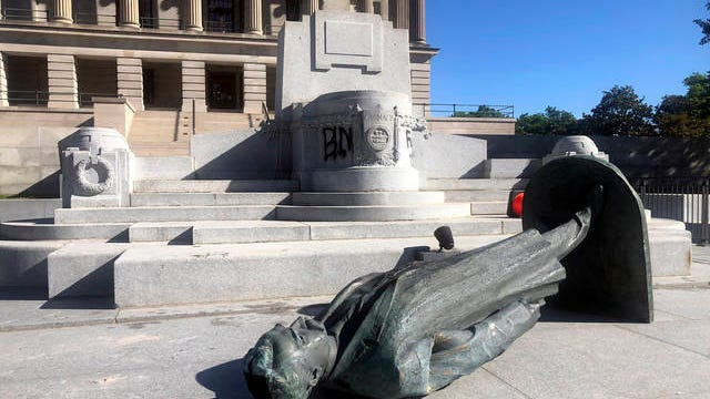 Protesters toppled the statue of Edward Carmack outside the state Capitol after a peaceful demonstration turned violent, Sunday, in Nashville.
