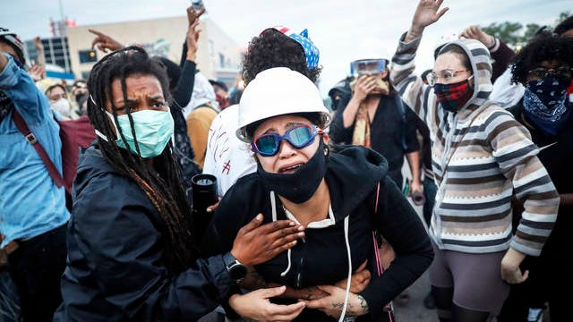 A protester reacts after being hit by crowd dispersal rounds as a group of demonstrators are detained prior to arrest at a gas station on South Washington Street on Sunday in Minneapolis. Protests continued sparked by the death of George Floyd, who died after being restrained by Minneapolis police officers on May 25.