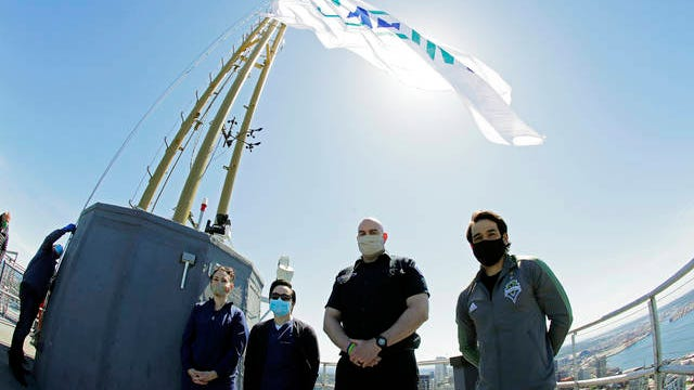 """From left, Sydney Hanson, and Vincente Yu, both nurses at EvergreenHealth in Kirkland, Wash., stand with Michael Allan, a firefighter with the Kirkland (Wash.) Fire Department, and Seattle Sounders captain and MLS soccer midfielder Nicolas Lodeiro after they took part in a flag raising for the launch of the """"All In WA"""" relief effort on May 27 on the roof of the Space Needle in Seattle. The statewide """"All In WA"""" campaign is backed by community and business organisations aiming to support workers and families who have been affected by the coronavirus outbreak."""