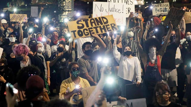 Demonstrators use their phone lights Wednesday in downtown Los Angeles during a protest over the death of George Floyd, who died May 25 after he was restrained by Minneapolis police.