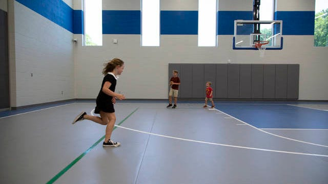 Children play inside the gymnasium at Battle Creek Elementary School in Spring Hill during an open house for the school on Saturday, July 27, 2019.