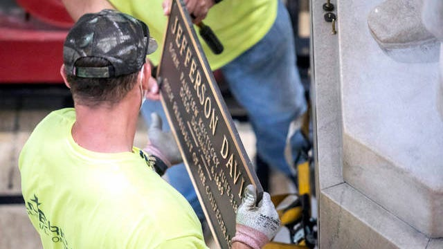 Workers remove a plaque from the Jefferson Davis statue in the Kentucky state Capitol in Frankfort, Ky., on Friday. A Kentucky commission voted Friday to take down a statue of Confederate President Davis from the state Capitol, adding its voice to a global push to remove symbols of racism and slavery.