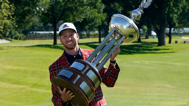 Daniel Berger poses with the championship trophy after winning the Charles Schwab Challenge golf tournament after a playoff round at the Colonial Country Club in Fort Worth, Texas on Sunday.
